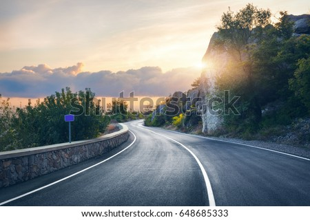 Mountain road. Landscape with rocks, sunny sky with clouds and beautiful asphalt road in the evening in summer. Vintage toning. Travel background. Highway in mountains. Transportation #648685333
