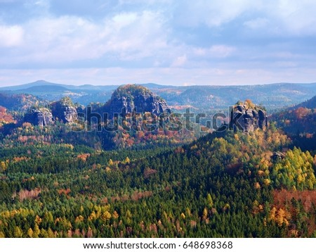 Autumnal sunrise in a beautiful mountain of Czech-Saxony Switzerland. Sandstone peaks increased from misty background, the fog is orange due to sun rays.  #648698368