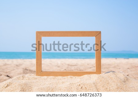 Photo frame on sand beach