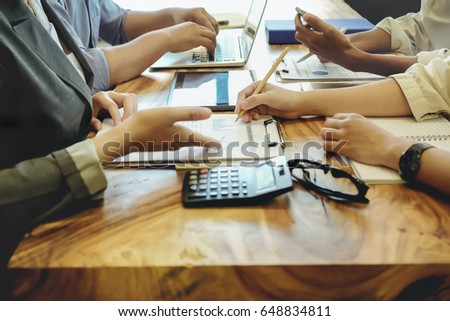 Business people pointing to financial graph in the conference.Business meeting time working with new startup project.Notebook and laptop on wood table.presentation concept, Accounting analyze plans. #648834811