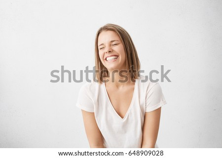 Positive human emotions. Headshot of happy emotional teenage girl with bob haircut laughing from the bottom of her heart, keeping eyes closed, showing perfect white teeth while having fun indoors #648909028