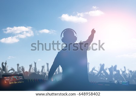 Charismatic disc jockey. Club, disco DJ playing and mixing music for crowd people. Royalty-Free Stock Photo #648958402