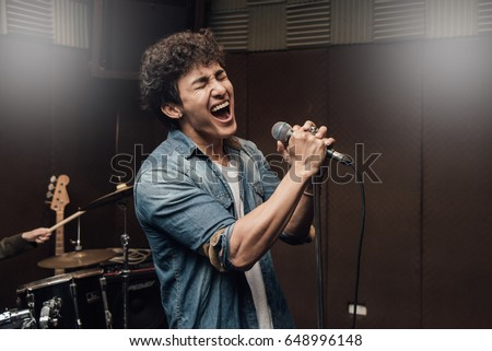 Male lead vocalist singing in studio with music instrument background. #648996148