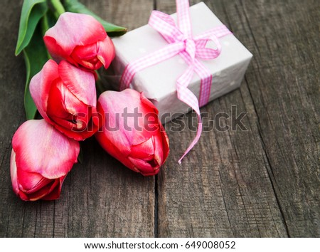 Spring tulips flowers and gift box on a old wooden  background #649008052