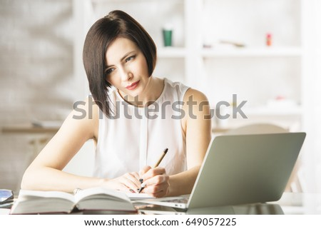 Portrait of beautiful young european lady doing paperwork and using laptop in modern office. She is working on project #649057225