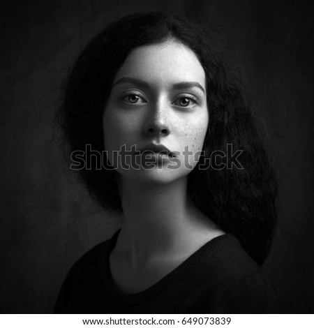 Dramatic black and white portrait of a beautiful lonely girl with freckles isolated on a dark background in studio shot #649073839