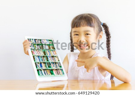 Asian girl pointing to her tablet, blur image of the bookshelf is on the screen.