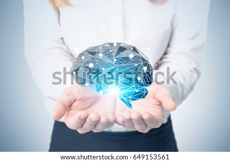 Front view of a blond businesswoman with a black brain hologram shining with a blue light hovering above her palms. Concept of an artificial intelligence