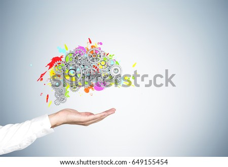 Close up of a businessman s hand in a white shirt holding a colored brain shape and gears on top of it drawn on a gray wall. Mock up #649155454