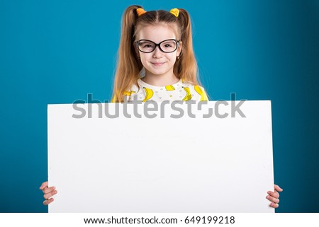 Little girl in glasses and banana T-Shirt with white board on blue background #649199218