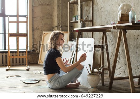 Woman painter sitting on the floor in front of the canvas and drawing. Artist studio interior. Drawing supplies, oil paints, artist brushes, canvas, frame. Workshop or art class. Creative concept Royalty-Free Stock Photo #649227229