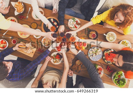 People clink glasses, saying cheers, eat healthy meals at party dinner table. Friends celebrate with organic food, ratatoille and corn barbecue on wooden table top view. #649266319