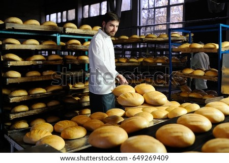 young handsome guy baker pulls out of the oven fresh bread at the bakery background #649269409