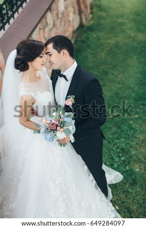 The charming brides keeping a wedding bouquet and embracing  in the yard #649284097