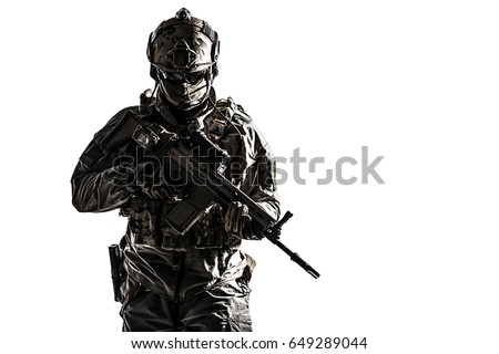 Army soldier in Protective Combat Uniform holding Special Operations Forces Combat Assault Rifle. Studio shot, dark contrast, cropped, desaturated, isolated on white background #649289044
