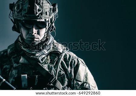 Elite member of US Army rangers in combat helmet and dark glasses. Studio shot, dark black background, looking at camera, dark contrast Royalty-Free Stock Photo #649292860
