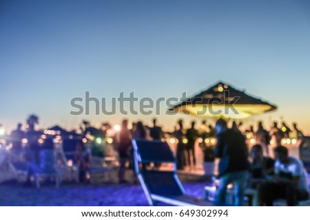 Blurred people having sunset beach party in summer vacation - Defocused image - Concept of nightlife with cocktails and music entertainment - Warm filter with blurry bokeh Royalty-Free Stock Photo #649302994