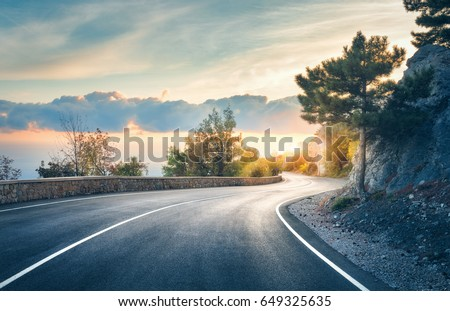 Mountain road. Landscape with rocks, sunny sky with clouds and beautiful asphalt road in the evening in summer. Vintage toning. Travel background. Highway in mountains. Transportation #649325635