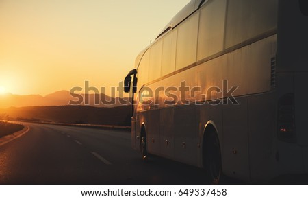 White bus driving on road towards the setting sun #649337458