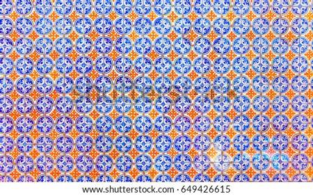 Beautiful blue and orange ornamental tiles pattern wall #649426615
