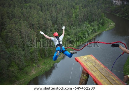 An extreme sportsman jumps on a rope from a great height. Ropejumping. #649452289