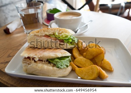 Sandwich with grilled chicken breast, tomato slices, lettuce and ketchup served with baked potato #649456954