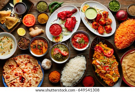 Assorted Indian recipes food various with spices and rice on wooden table Royalty-Free Stock Photo #649541308