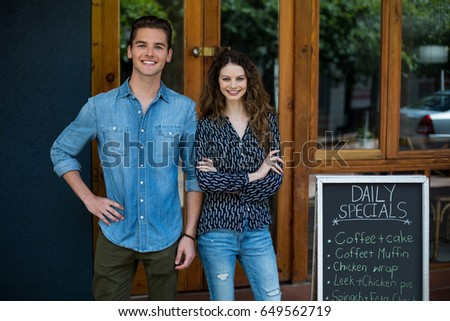 Portrait of smiling man and woman standing outside café beside the menu board #649562719