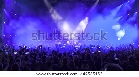 A crowd of people at a concert. Silhouettes of a crowd of fans in front of bright scene lights. #649585153