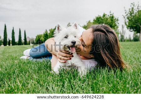 Beautiful young woman playing with her little west highland white terrier in a park outdoors. Lifestyle portrait. #649624228