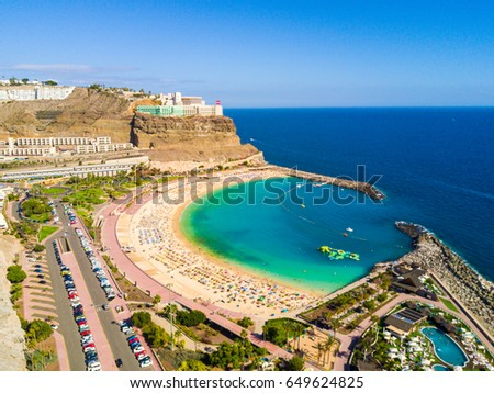 Amazing aerial view of Playa de Amadores beach on the Gran Canaria island in Spain. Beautiful sea shore with cliffs of the island. #649624825