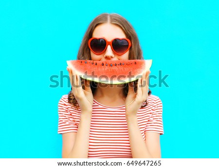 portrait happy young woman is holding slice of watermelon over colorful blue background #649647265