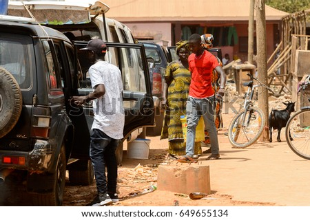 CANCHUNGO, GUINEA BISSAU - MAY 3, 2017: Unidentified local man in white shirt stands near the car in the centre of Canchungo, one of the major cities of the country #649655134