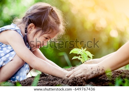 Asian little girl and parent planting young tree on black soil together as save world concept in vintage color tone #649767436
