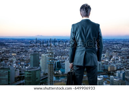 businessman looking down a modern city. business prospect concept. #649906933