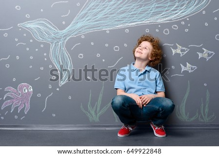 Happy boy under the sea. Surprised child looking at a whale, octopus and flock of fish depicted with chalk on gray wall.