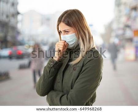 Health care concept. Young woman in face mask on city street #649968268