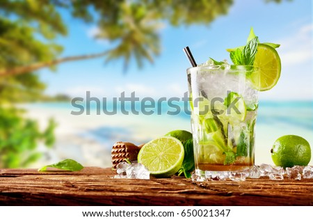 Fresh mojito drink placed on wooden planks, blur tropical beach on background. Summer drinks and beach vacation background #650021347