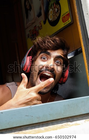 Bangkok, Thailand - May 29, 2017 : The european tourist in humorous action to take a photo with assuming eyes and laughing on his face. #650102974