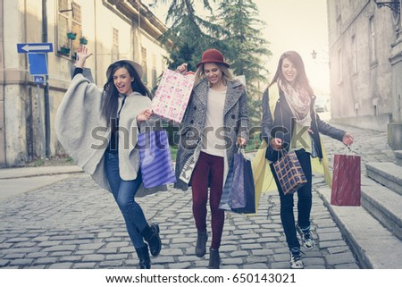 Three best friends running on the street . Young females best friends doing shopping on the streets. Females running trough street. #650143021
