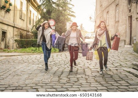 Three best friends running on the street . Young females best friends doing shopping on the streets. Females running trough street. #650143168