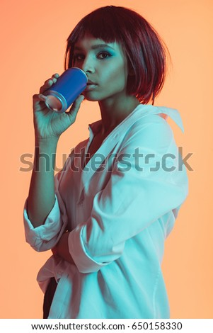 portrait of young pensive african american woman drinking from can #650158330