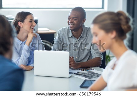 Male and female graphic designers interacting with each other in office #650179546