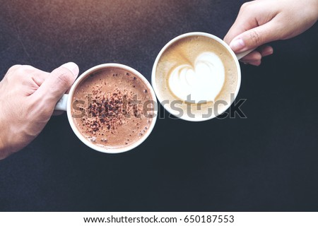 Top view image of man and woman's hands holding coffee and hot chocolate cups with wooden table background