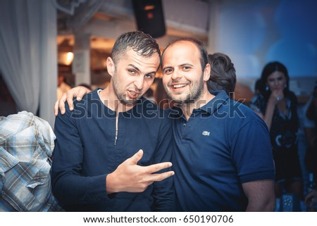 Odessa, Ukraine June 28, 2014: Ibiza night club. People smiling and posing on cam during concert in night club party. Man and woman have fun at club. Boy and girl at night club party #650190706
