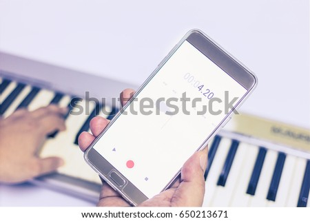 Mobile phone is recording the sound of man playing piano #650213671