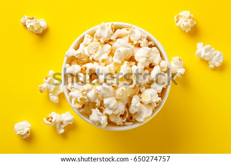 Popcorn viewed from above on yellow background. Flat lay of pop corn bowl. Top view Royalty-Free Stock Photo #650274757