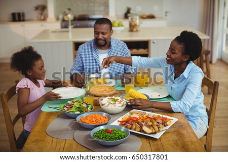 Happy family having meal on dinning table at home #650317801
