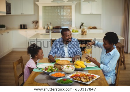 Happy family having meal on dinning table at home #650317849