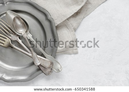 Various silverware on a pewter plate and gray flax napkin are on the background of gray concrete surface, with copy-space #650341588